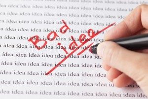 "Woman's hand with red pen writing words ""Bad idea"" on the background of words ""idea""."